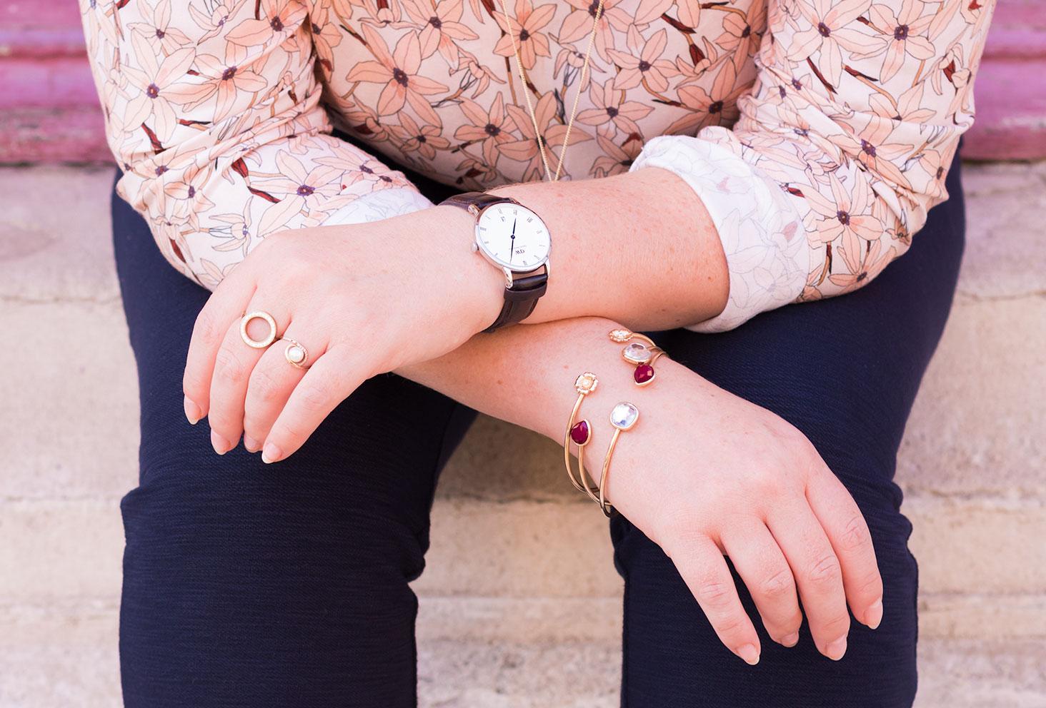 Les coudes appuyés sur les genoux, zoom sur la montre marron en cuir Daniel Wellington et les bijoux dorés MOA Paris portés