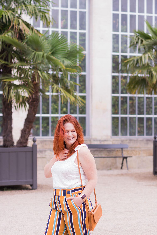 Devant les palmiers et la verrière du jardin botanique de Tours, de profil en débardeur et pantalon fluide jaune, avec la pochette sur l'épaule