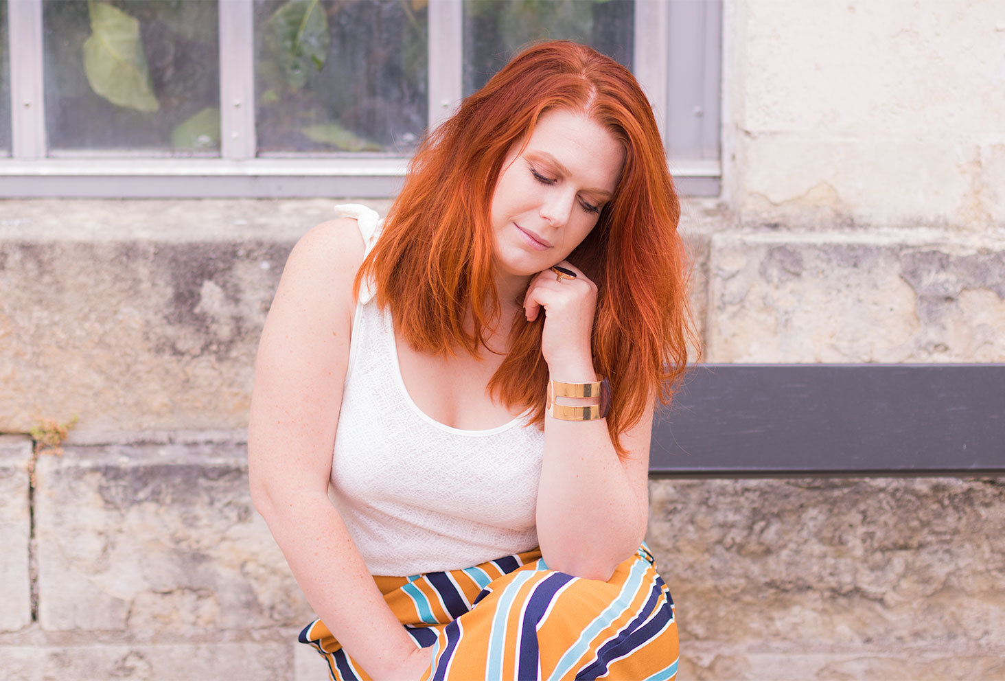 Assise sur un banc de face, le coude appuyé sur la cuisse et la tête appuyé sur la main, les cheveux longs roux détachés en débardeur blanc
