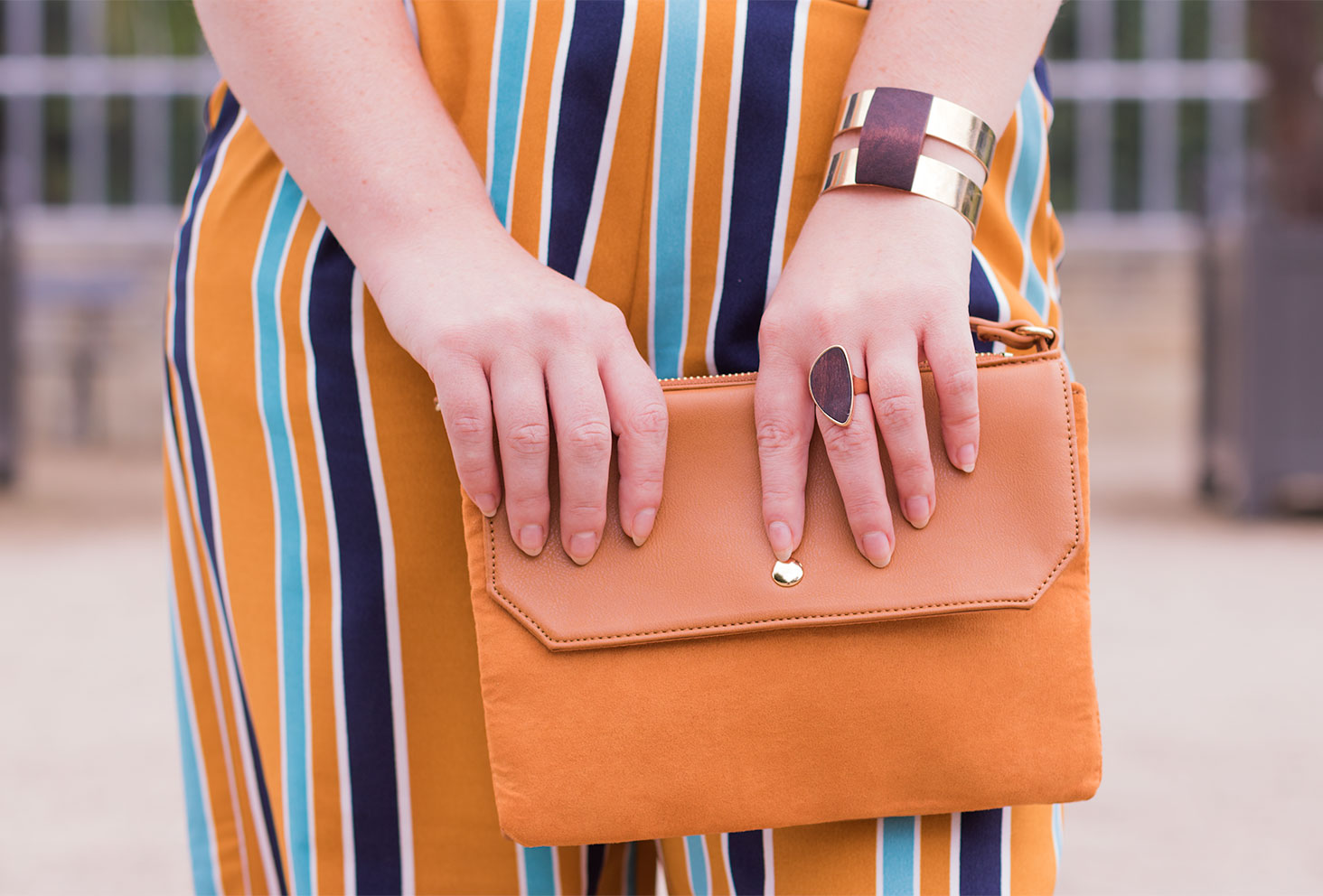Une pochette camel de Kiabi tenue entre les mains devant un pantalon jaune à rayure