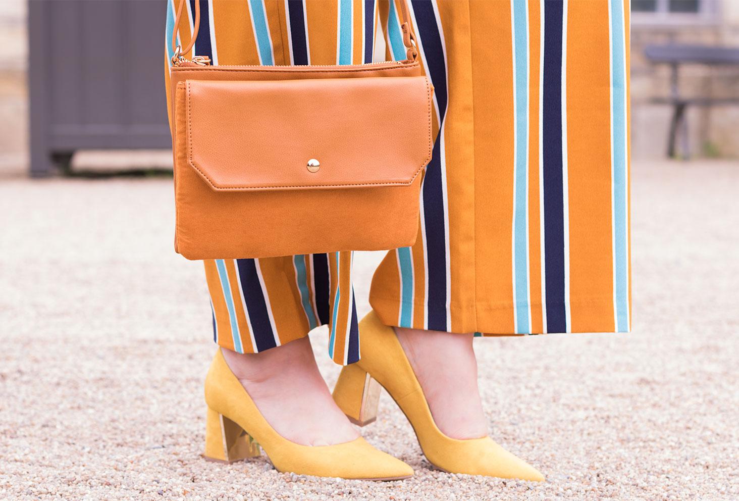 Pochette Kiabi portée devant un pantalon fluide jaune à rayures et escarpins jaunes