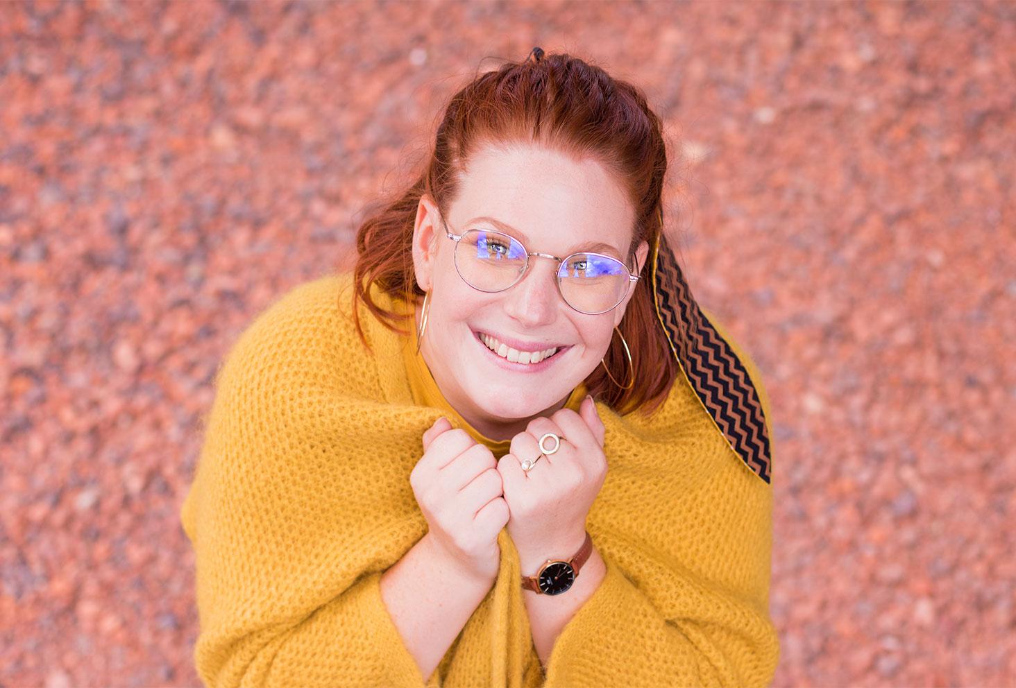 Portrait avec le sourire de haut, le gilet jaune en laine porté serré entre les deux mains à l'avant
