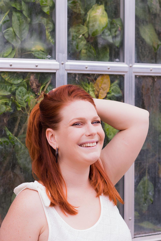 Portrait de profil, les cheveux relevés en demi queue avec la main, avec le sourire devant une verrière