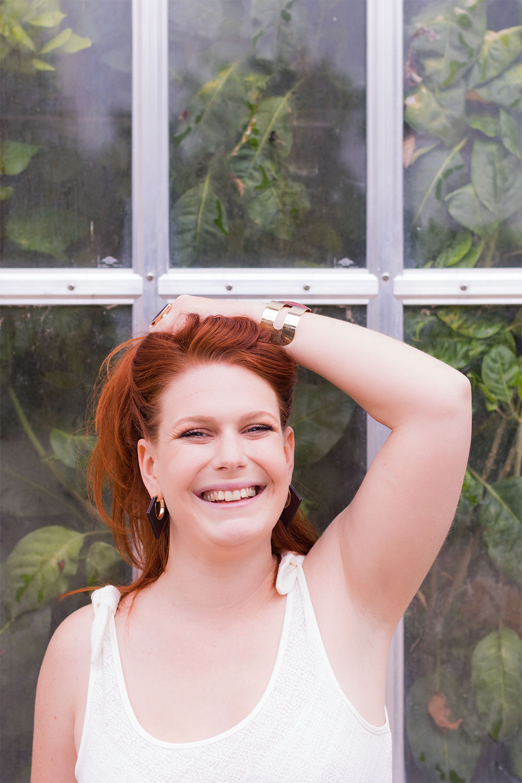 Portrait devant une verrière, les cheveux roux relevés par la main, avec le sourire en débardeur en dentelle blanc