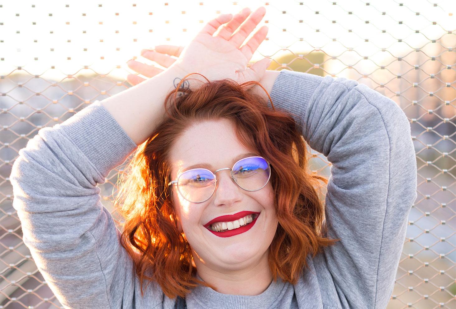 Portrait avec le sourire et les cheveux bouclés, les bras croisés derrière la tête