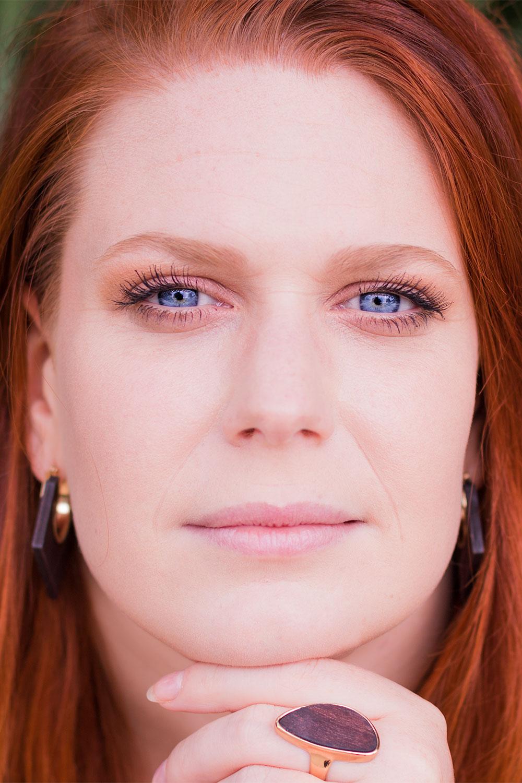 Zoom portrait avec boucles d'oreilles et bague en bois, yeux bleus et cheveux roux