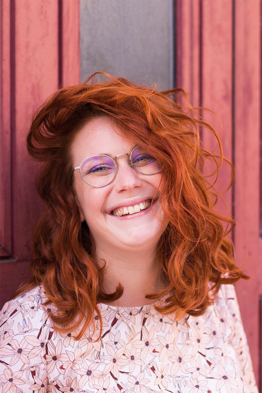 Photo portait serré, cheveux roux énormément bouclés, avec un grand sourire aux lèvres et des yeux bleus cachés derrière de grosses lunettes de vue