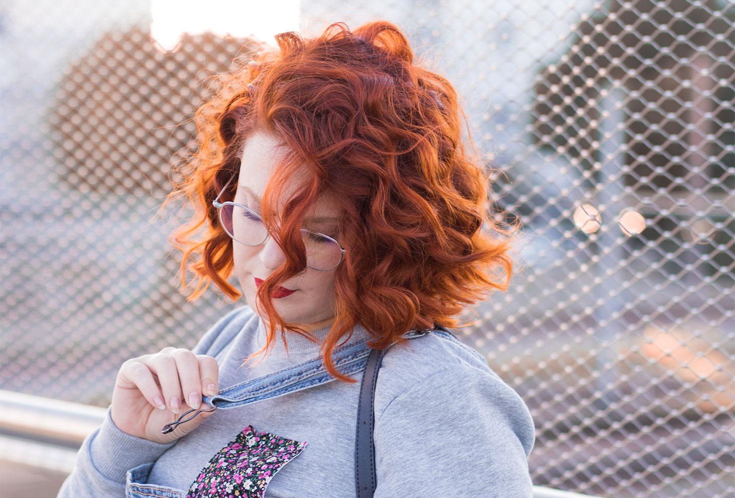 Zoom sur les cheveux roux bouclés de profil, entrain de rattacher la bretelle de la salopette en jeans par dessus le sweat Wazashirt