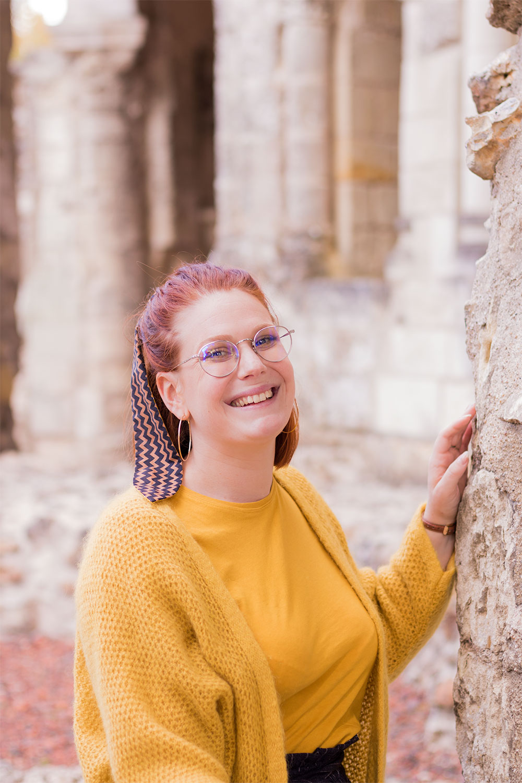 La main appuyée le long d'un mur en pierre, le sourire au lèvres et les cheveux attachés en arrière avec un noeud noir et marron, en gilet et t-shirt jaune