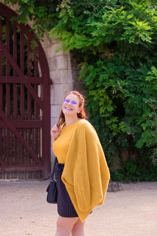 De profil avec le gilet jaune sur l'épaule, devant un portail en bois