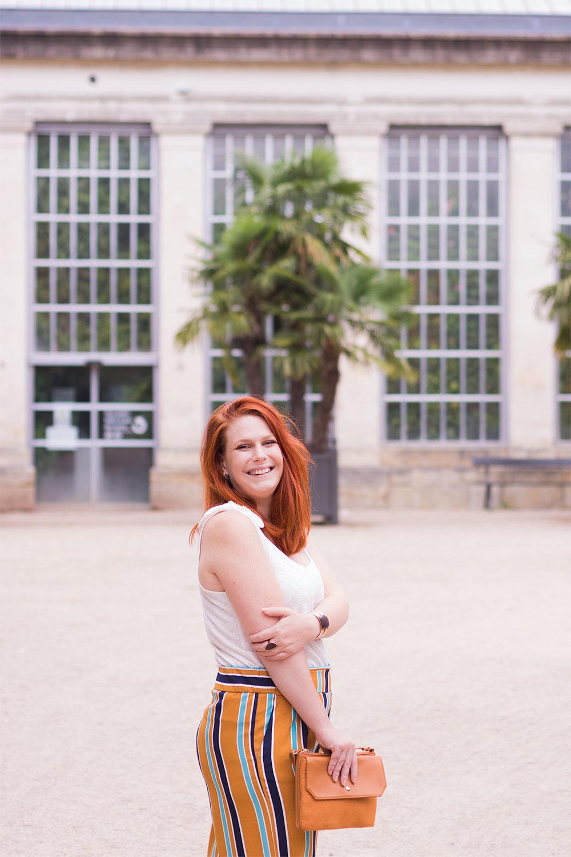 De profil devant les palmiers, en pantalon fluide jaune, le sourire aux lèvres et pochette jaune dans les mains