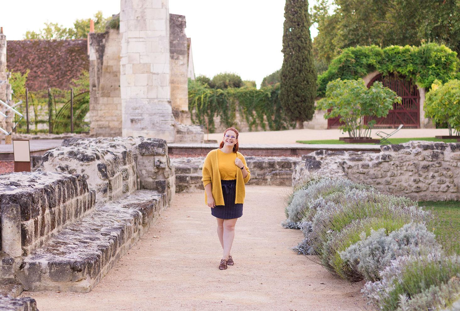 Au milieu des ruines en pierre, en jupe bleue et gilet jaune