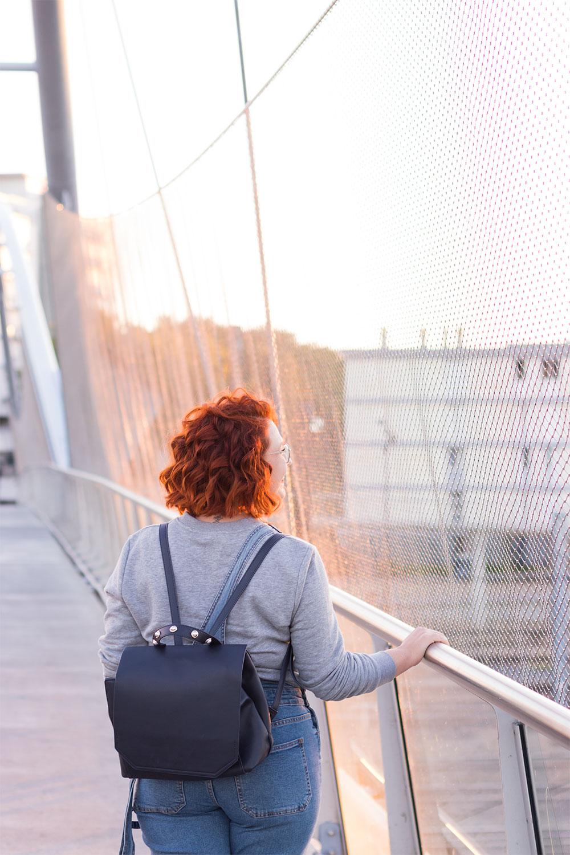 De dos avec le sac à dos noir Kiabi porté, en look street, au coucher du soleil