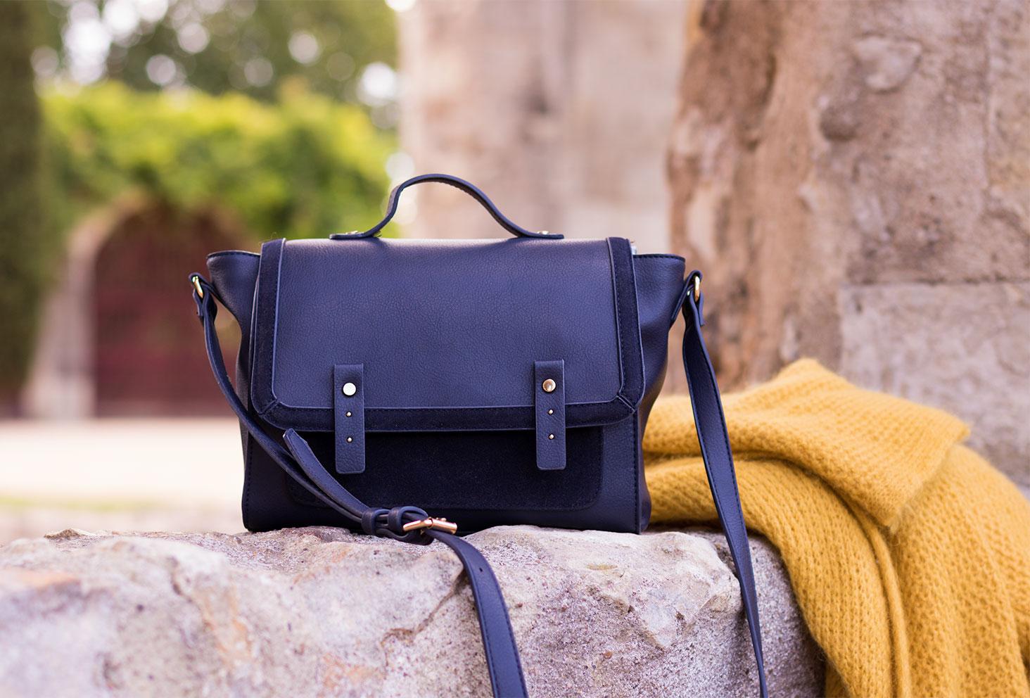 Zoom sur le sac en bandoulière en forme de cartable posé sur un mur en pierre à côté du gilet jaune en laine