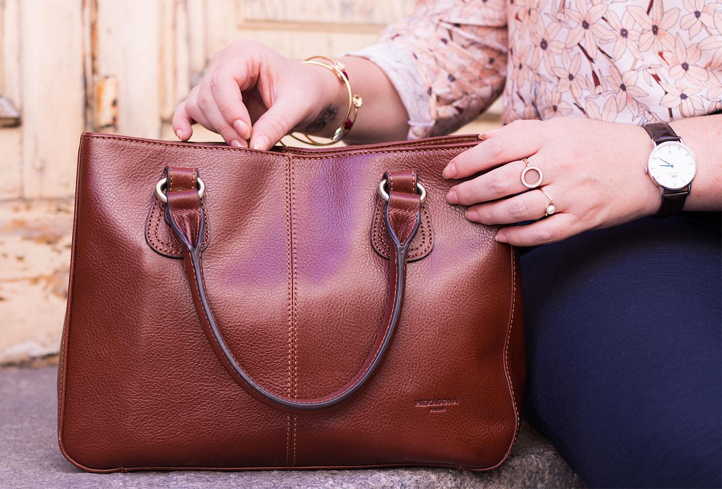 Zoom sur le sac marron en cuir Hexagona Paris posé sur des marches en pierre, les mains entrain d'ouvrir la fermeture