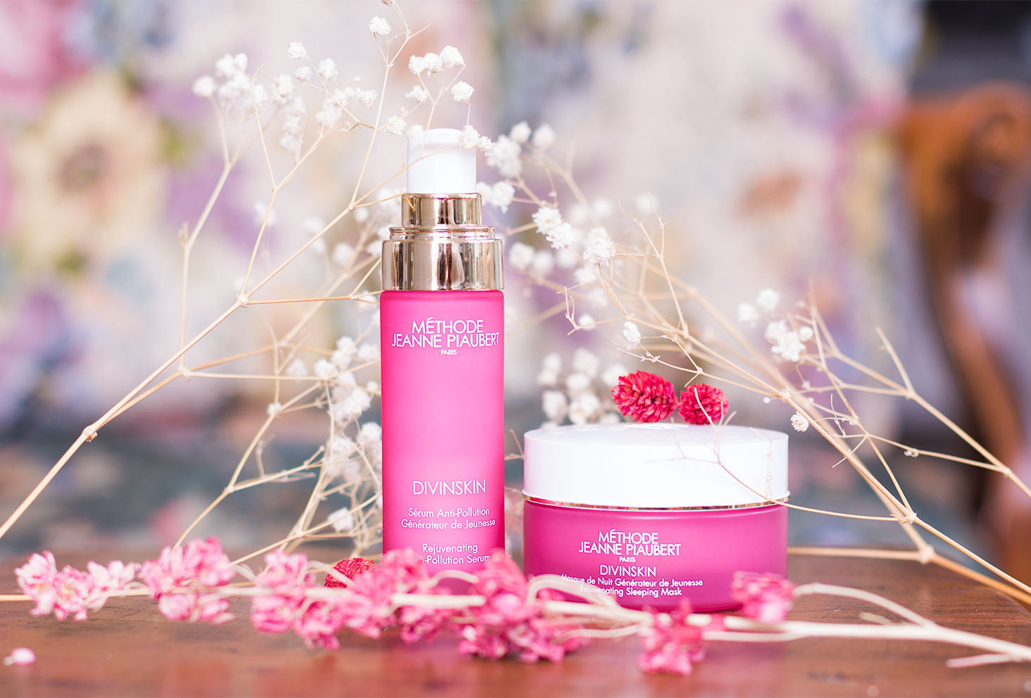 Le sérum anti-pollution et le masque de nuit de la Méthode Jeanne Piaubert sur un table en bois au milieu des fleurs séchées roses et blanches