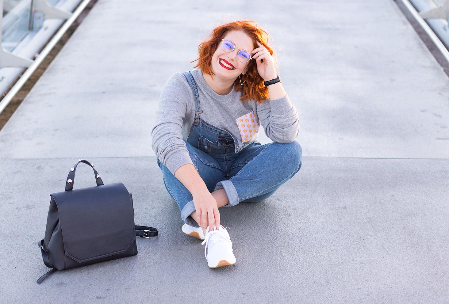 Assise par terre en look street au milieu d'une passerelle, avec le sac à dos noir posé à côté