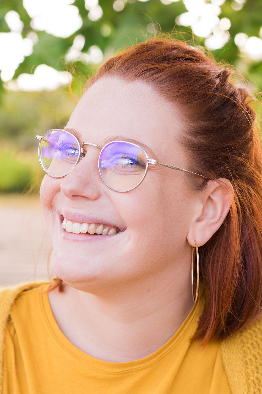 Zoom portrait sourire, lunette, yeux bleus et cheveux roux attachés en demi queue