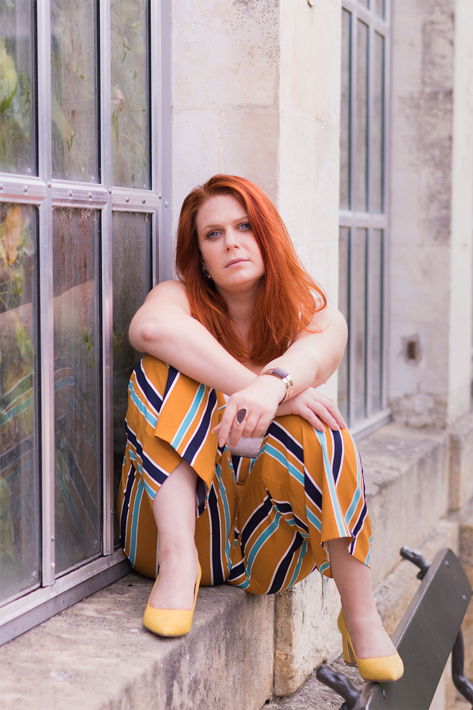 Assise en pose street sur un mur en pierre en pantalon fluide à rayures et escarpins jaunes