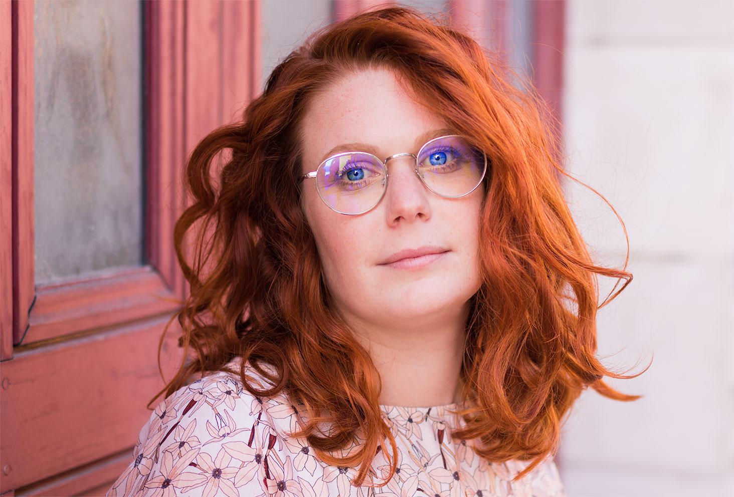 Portrait mélancolique, léger sourire et cheveux très bouclés roux, devant une porte orange