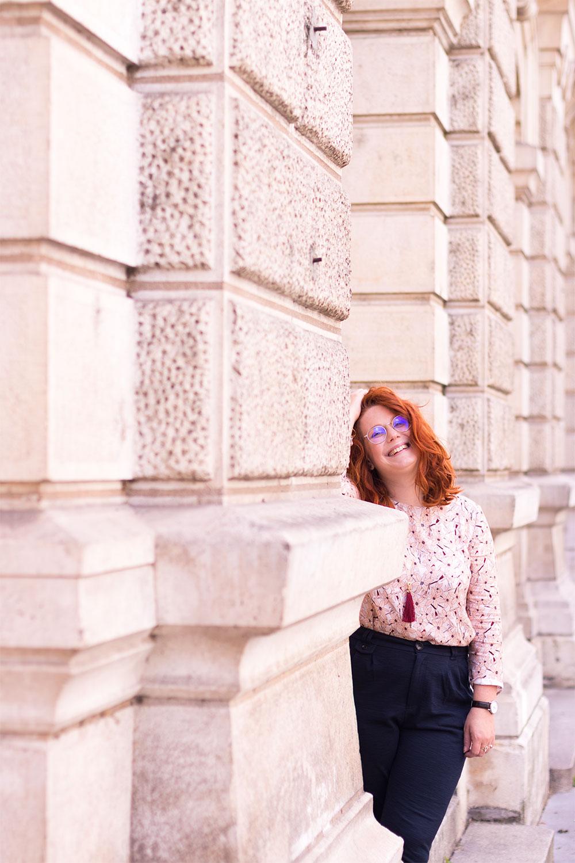 Cachée derrière un grand mur en pierre blanche en blouse rosée à fleurs légère La Morue et cheveux bouclés