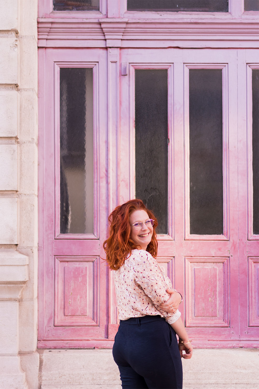 De dos, devant une porte en bois rose, en blouse La Morue et pantalon confortable bleu marine