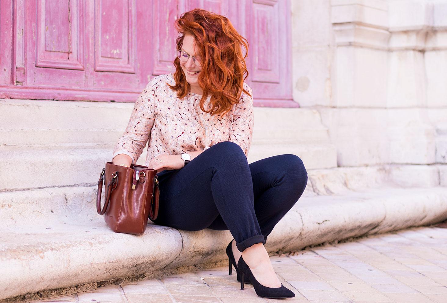 En train de chercher dans le sac marron en cuir Hexagona Paris assise sur des marches en vieilles pierres avec les cheveux roux très bouclés