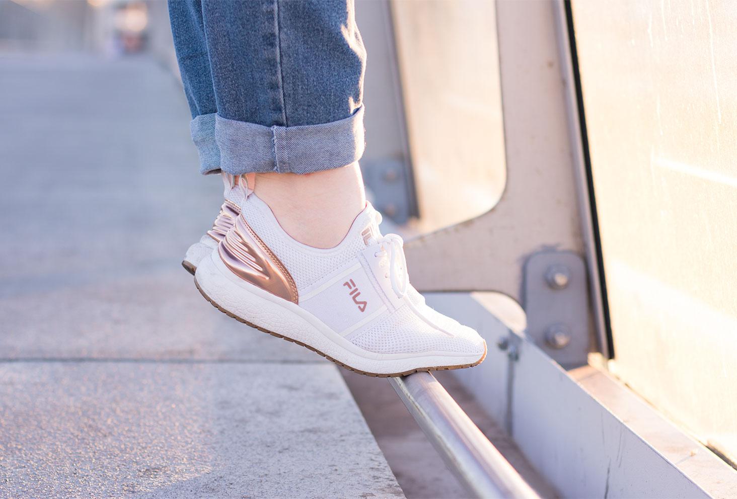 Zoom sur les baskets FILA blanche et dorée sur une rambarde en métal sur la pointe des pieds