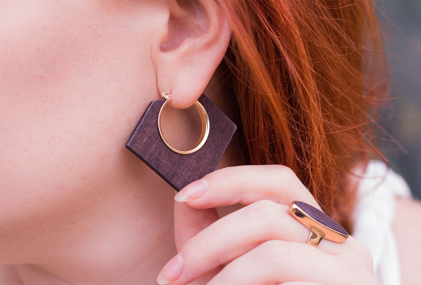 Zoom sur les boucles d'oreilles en bois carré portées