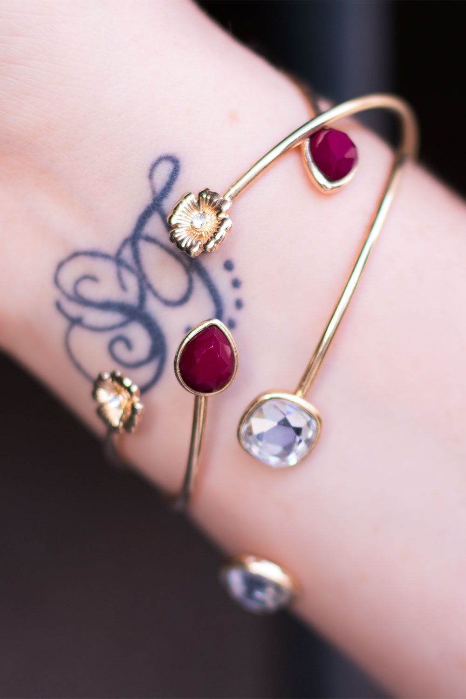 Zoom sur les bracelets dorés MOA Paris par dessus un tatouage à initiales S et F