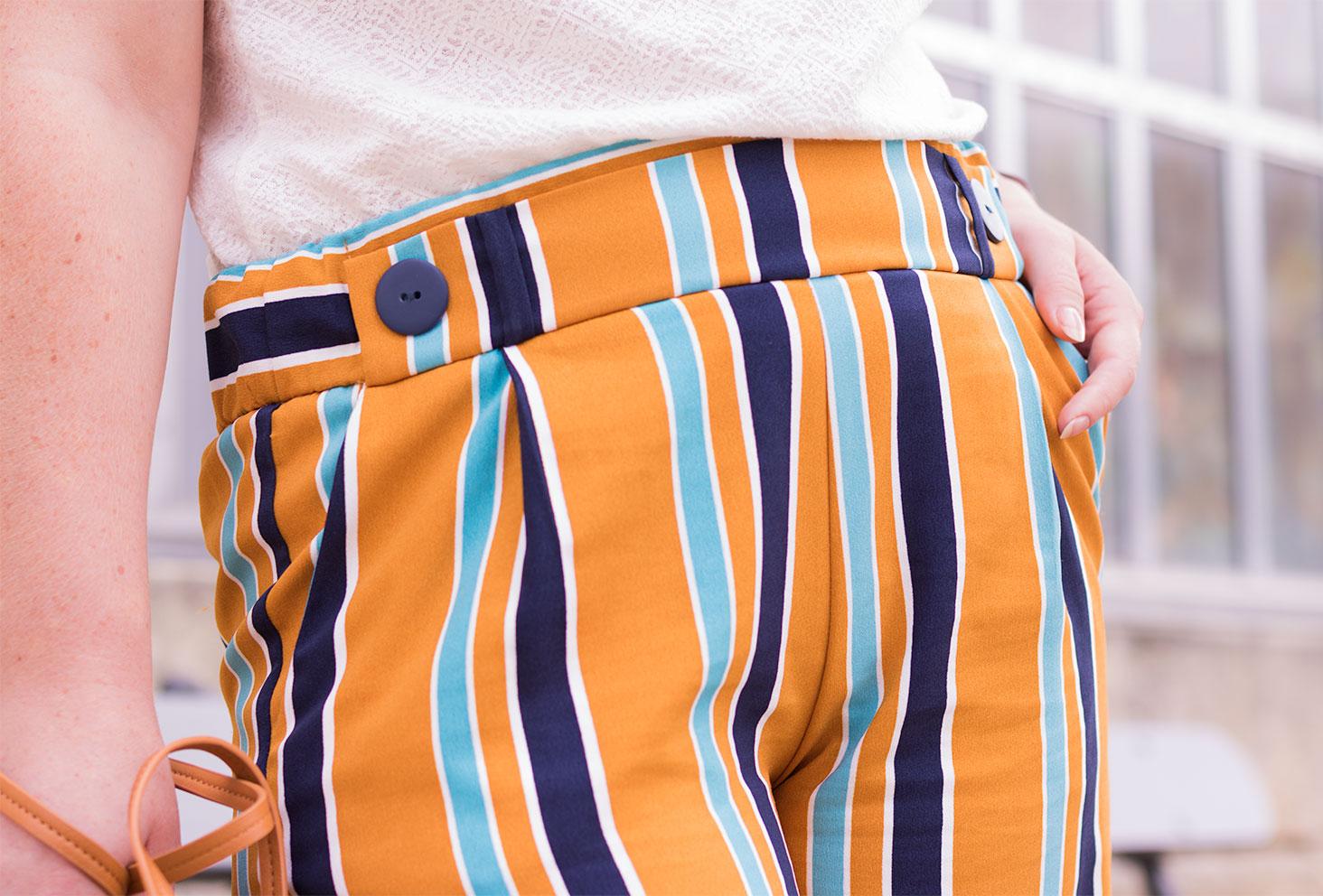 Zoom sur la ceinture du pantalon jaune à rayures Zara porté