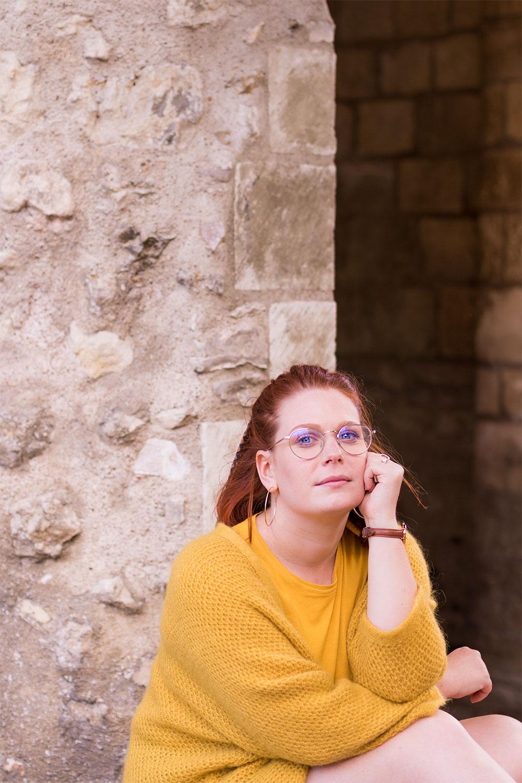 Assise le long d'un mur en pierre les bras appuyés sur les genoux, le visage posé sur la main