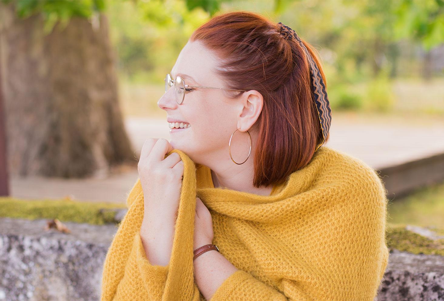 Bien au chaud dans un gros gilet jaune, assise sur une pierre, emmitouflée avec le sourire