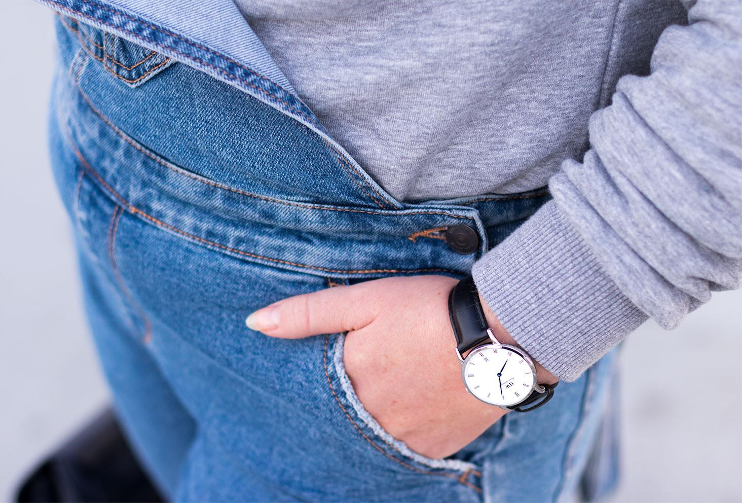 Zoom sur la Dapper noire de Daniel Wellington portée la main dans la poche de la salopette en jeans