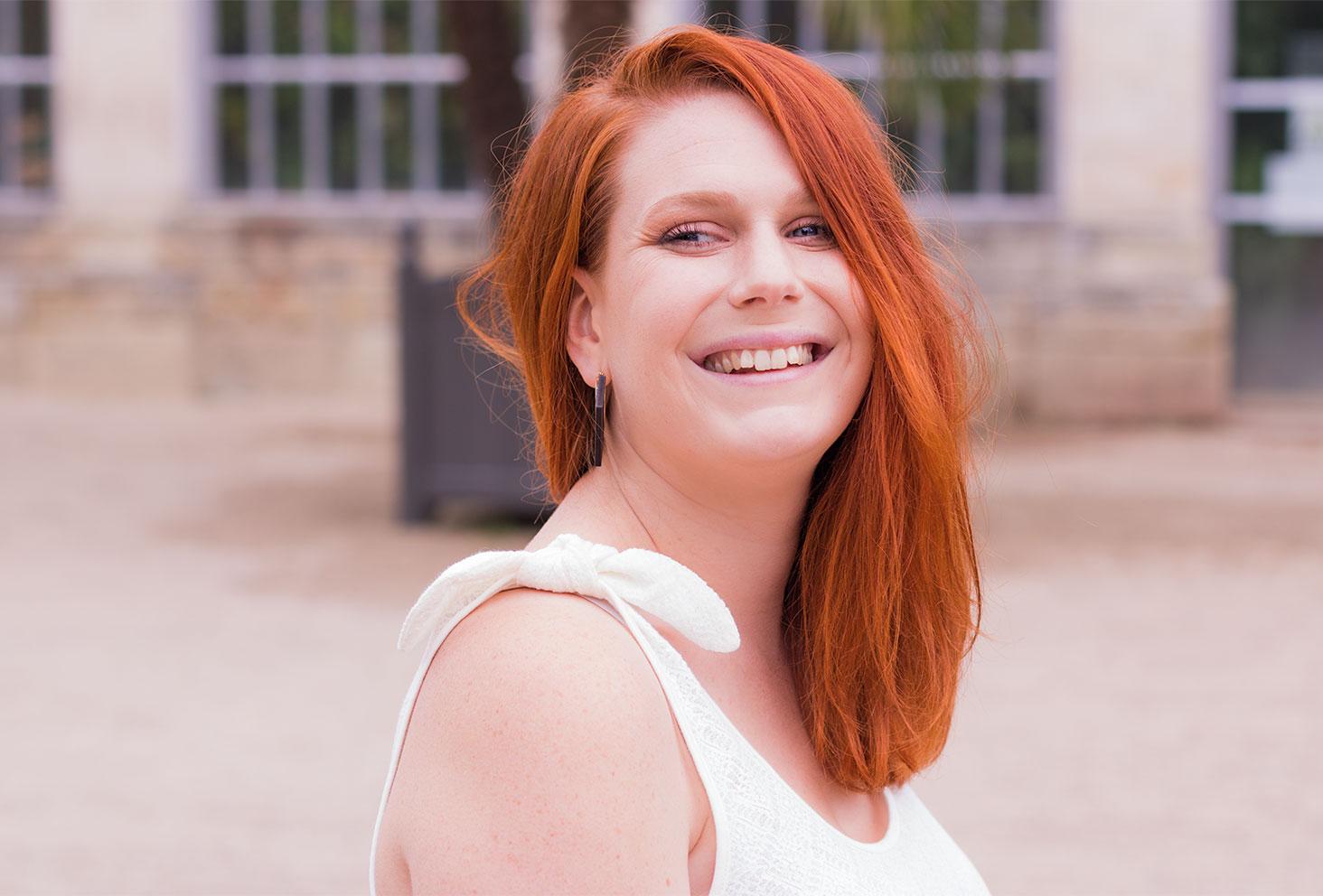 Portrait de profil, cheveux longs roux détachés et sourire aux lèvres, avec zoom sur le noeud des manches du débardeur blanc Kiabi