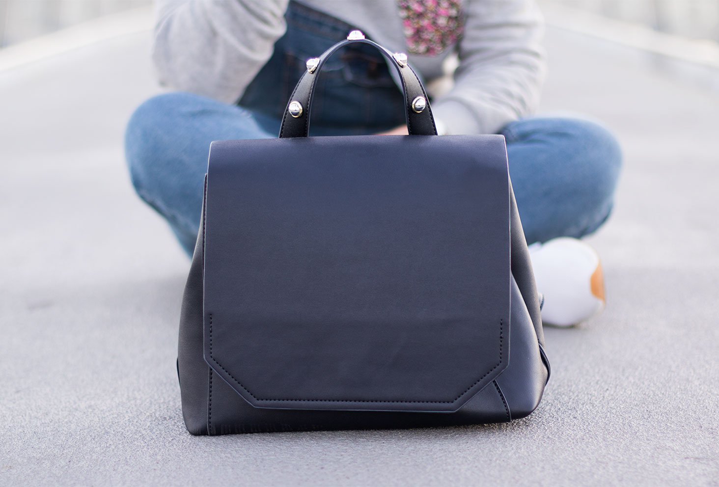 Zoom sur le sac à dos noir à clous Kiabi, posé sur le sol bétonné