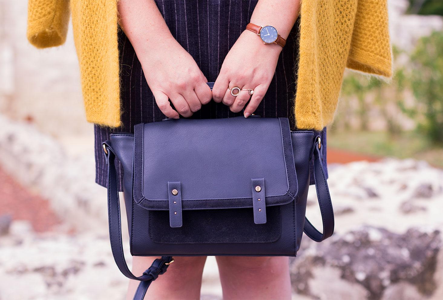 Zoom sur le sac bleu en forme de cartable Camaïeu tenu dans les deux main devant les jambes