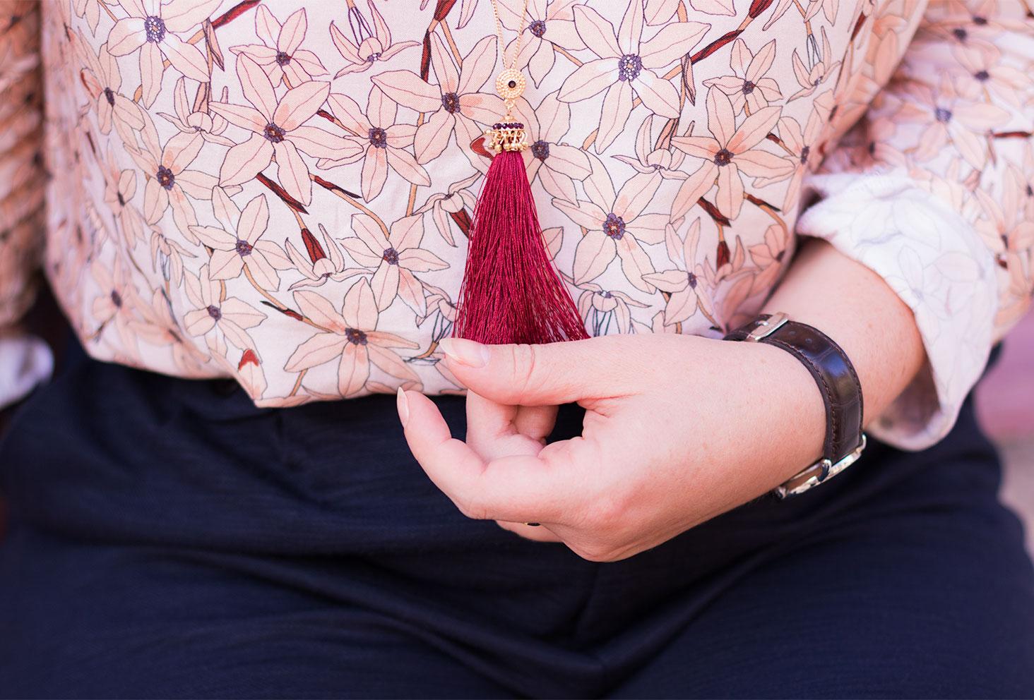 Zoom sur le pompon du sautoir MOA bordeaux portés et tenu dans une main devant la blouse fleurie La Morue