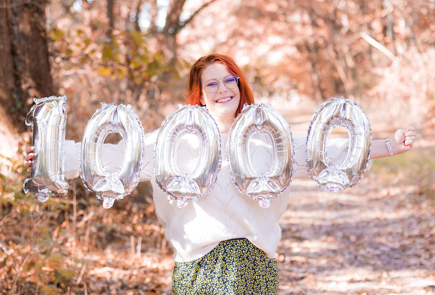 Les ballons argentés dans les bras au milieu de la forêt pour les 10000 abonnés