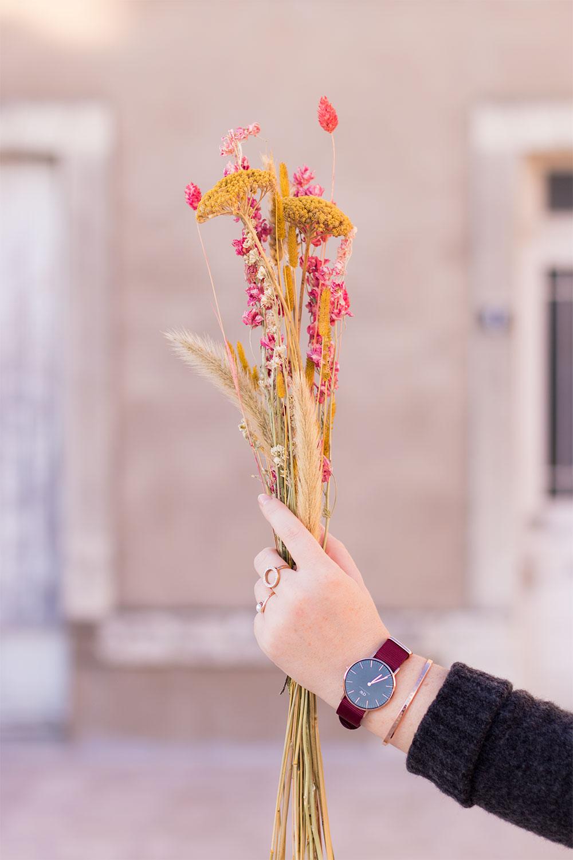 La montre Classic Black Roselyn de Daniel Wellington portée avec un bouquet de fleurs sèches dans les mains