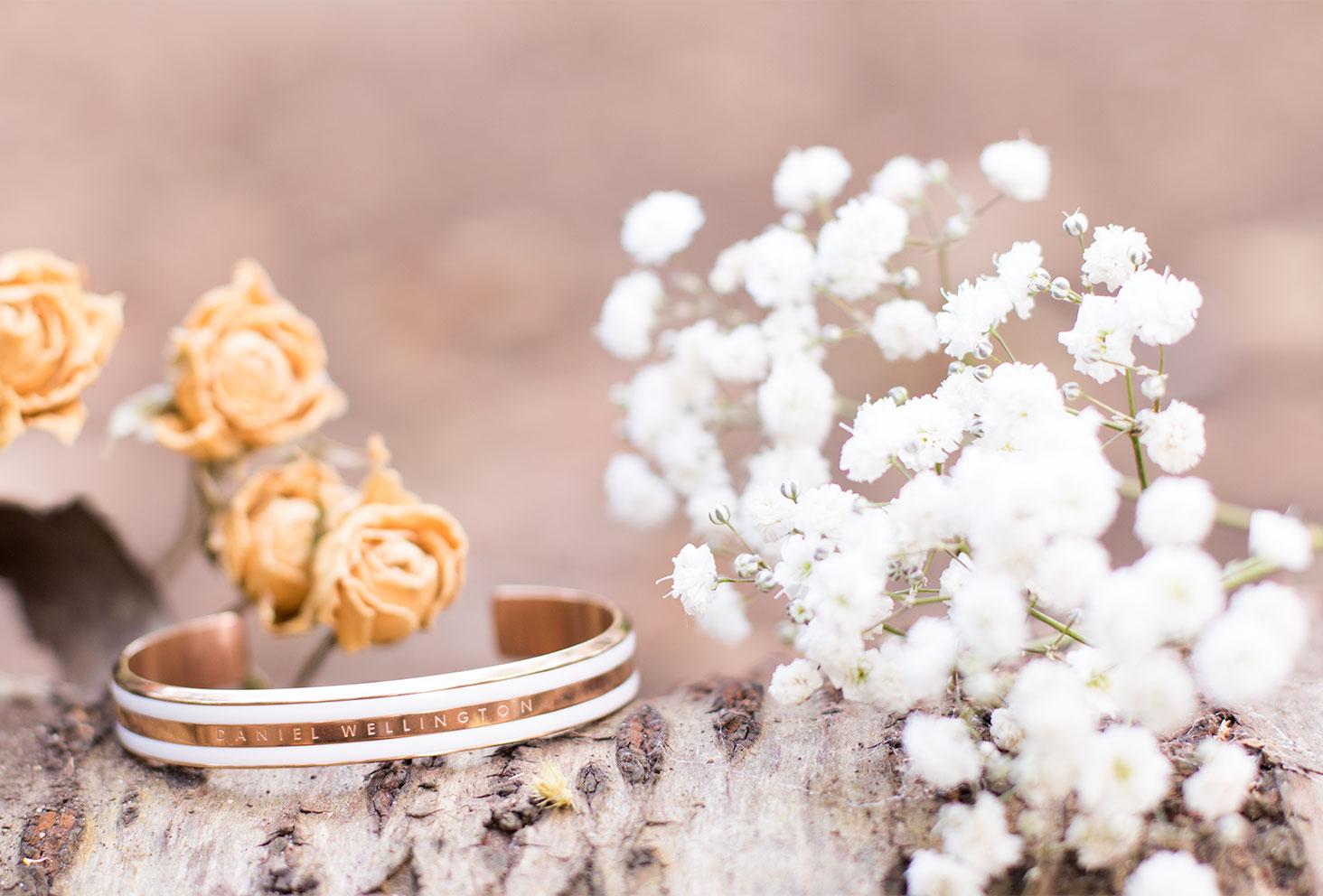 Le Classic bracelet blanc et doré de Daniel Wellington posé sur une souche d'arbre au milieu des fleurs séchées blanches et jaunes