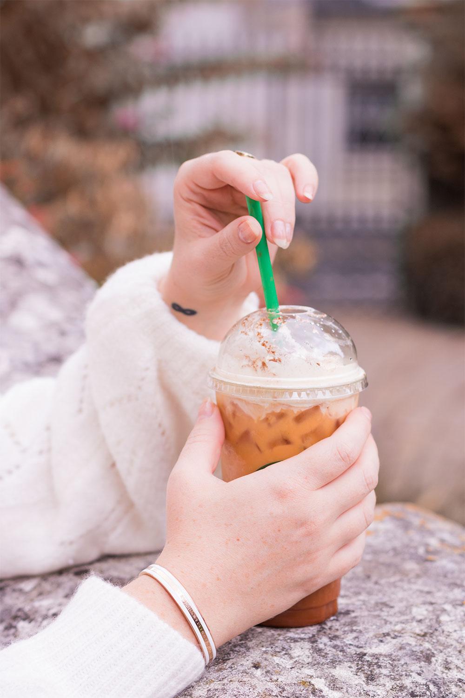 Le Classic bracelet blanc et doré de Daniel Wellington porté avec un pull blanc et un Starbucks dans la main