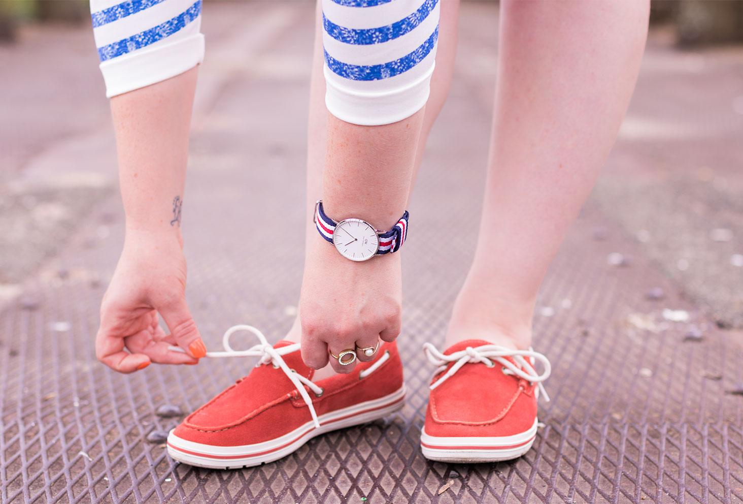 La montre Classic Cunterbury portée dans un look so french, en marinière entrain de lacet des chaussures bateau rouges