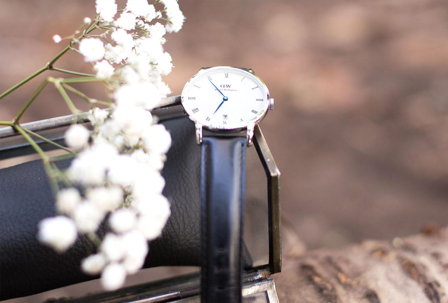 La montre Dapper Shefield de Daniel Wellington posée sur la boîte à rangement en verre au milieu des fleurs séchées blanches