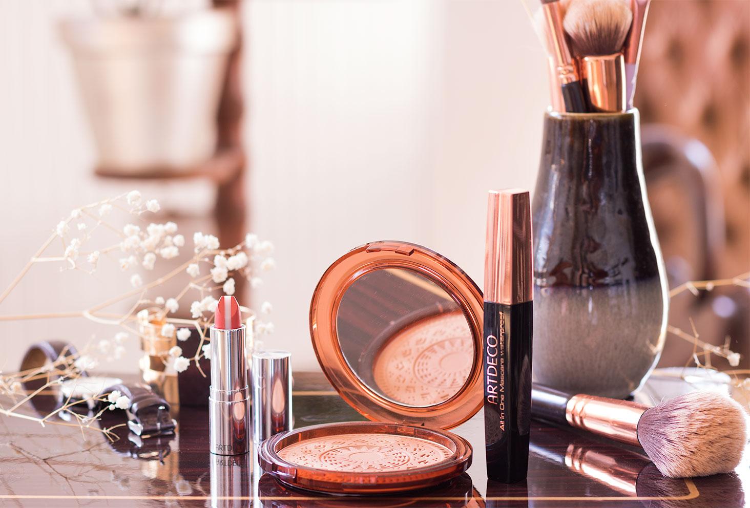 Le rouge à lèvres, la poudre bronzante et le mascara ARTDECO sur une table en bois vernis foncé au milieu des pinceaux à maquillage et des fleurs séchées