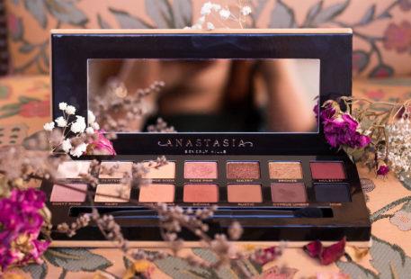La palette Soft Glam d'Anastasia Beverly Hills ouverte de face, au milieu de fleurs séchées sur un vieux fauteuil vintage