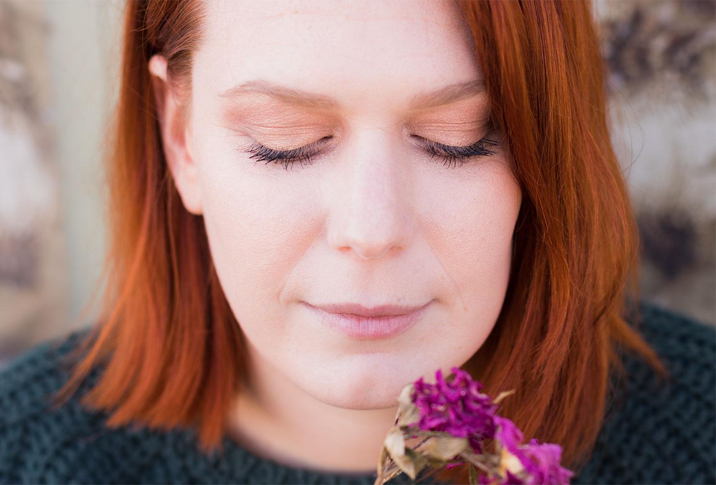 De face les yeux fermés, des fleurs séchées violettes dans les mains, zoom sur le make-up réalisé avec la palette Soft Glam d'Anastasia Beverly Hills