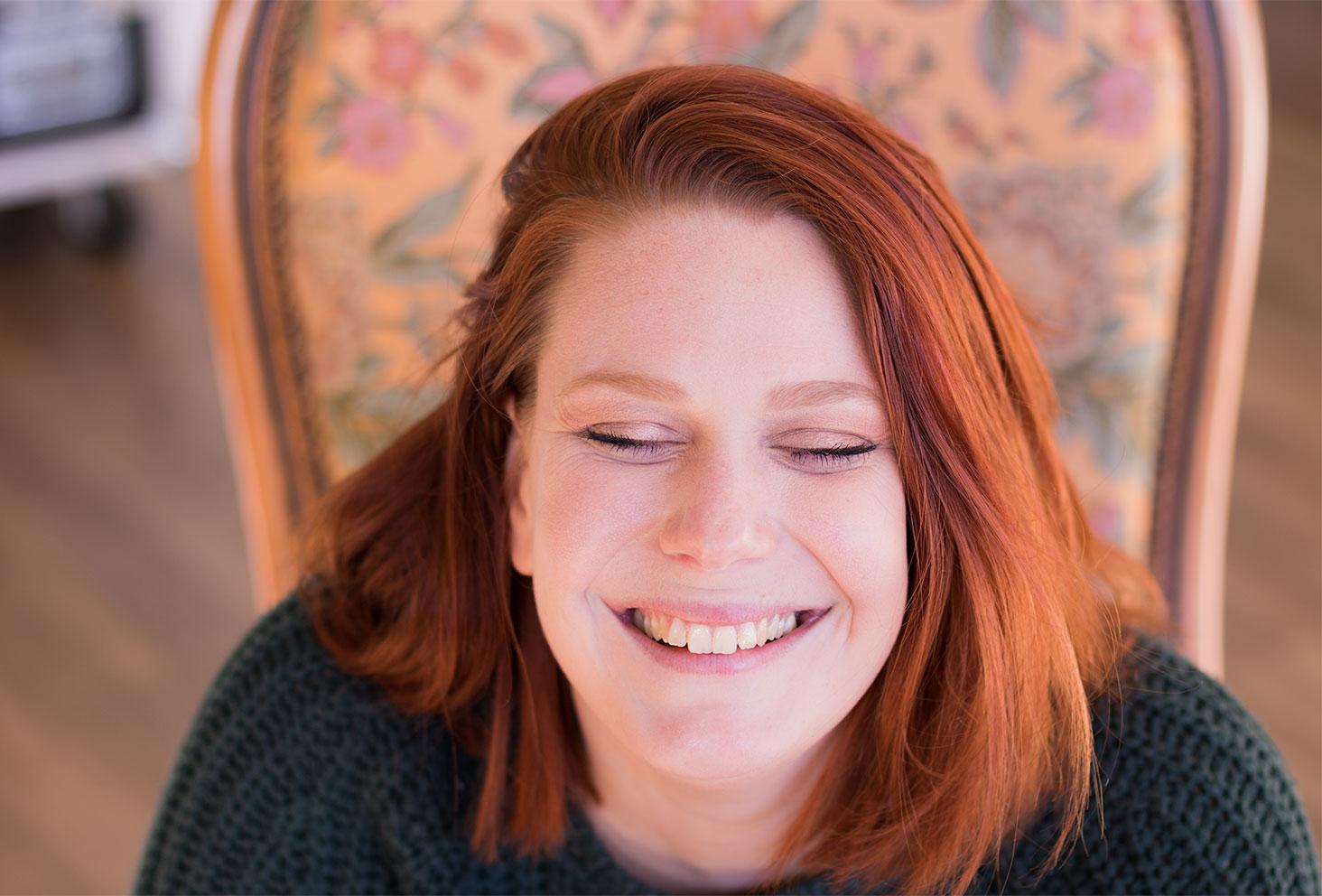 De haut assise sur un vieux fauteuil en tissu fleurit, le sourire jusqu'aux oreilles, make-up avec la palette Soft Glam