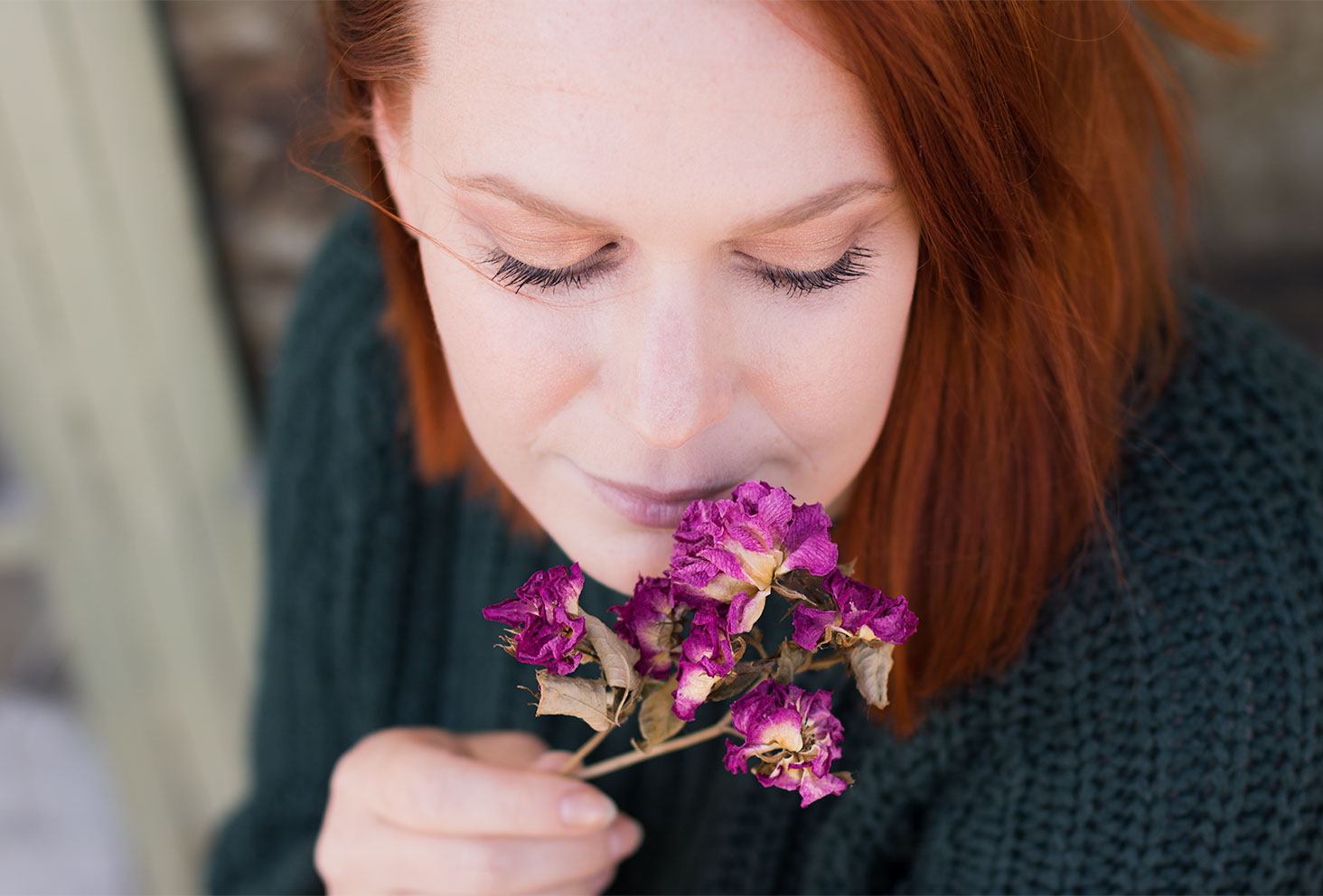 Zoom sur le make-up réalisé avec la palette Soft Glam, des fleurs sèches violettes dans la main près du visage