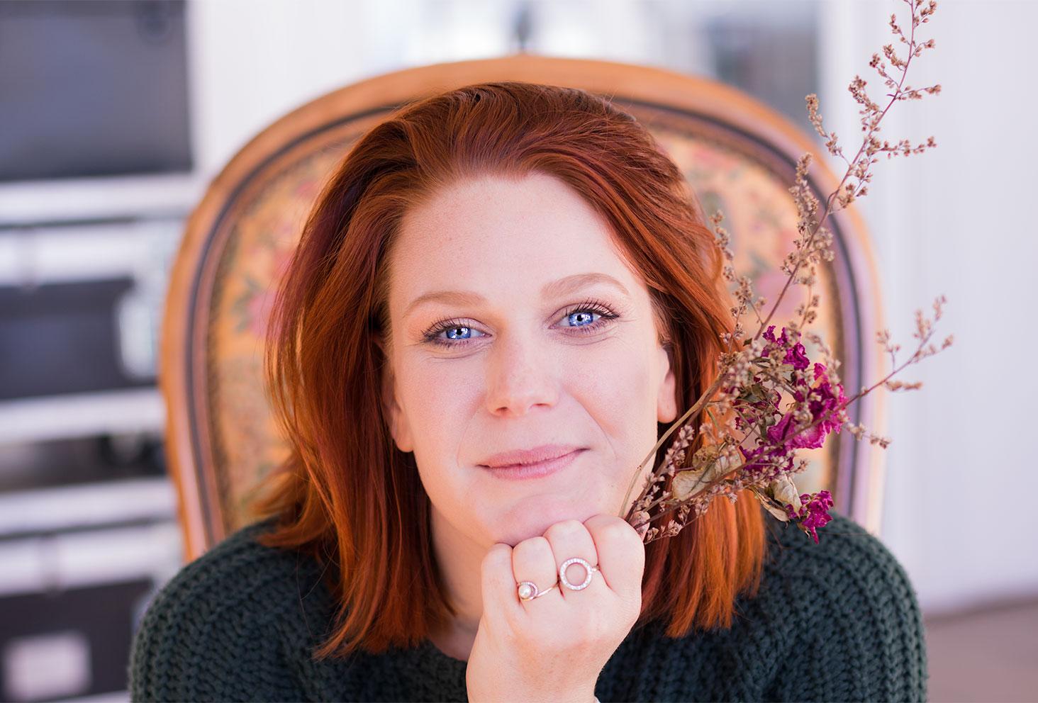 Cheveux roux et yeux bleus, make-up réalisé avec la palette Soft Glam d'Anastasia Beverly Hills, le menton dans la main avec un bouquet de fleurs sèches